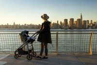 Side view of woman looking at city skyline while standing on promenade with baby carriage during sunset