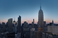 Empire State Building amidst cityscape against clear blue sky at dusk