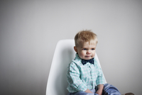 Sad baby boy sitting on chair against white wall at home