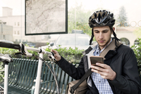 Male commuter using smart phone while sitting at bus stop