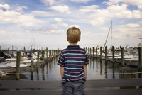 Rear view of boy standing on bridge by harbor against cloudy sky