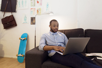 Illustrator using laptop while sitting on sofa in creative office