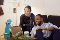 Happy male and female illustrators using laptop in creative office 11100037574| 写真素材・ストックフォト・画像・イラスト素材|アマナイメージズ