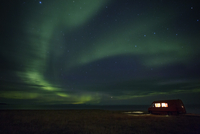 Illuminated van parked at sea shore against Aurora Borealis