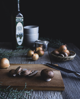 Button mushrooms with onion and knife on cutting board