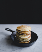 Stack of pancakes in frying pan on marble counter