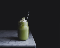 Close-up of matcha shake in bottle on marble counter against black background