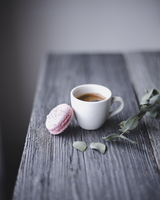 Close-up of pink macaroon and coffee cup on wooden table