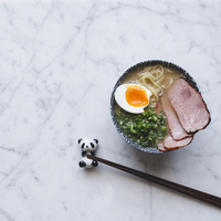 High angle view of ramen noodles soup with pork served in bowl on counter