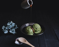 Honey being poured on thick matcha icecream in plate at wooden table
