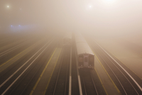 Train on illuminated railroad tracks at dusk in foggy weather