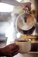 Cropped image of barista pouring coffee in cup at cafe