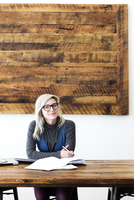 Portrait of young businesswoman sitting at wooden table in office