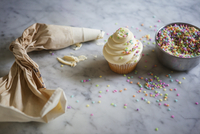 High angle view of icing bag by cupcake and sprinkles on kitchen counter