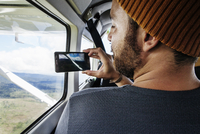 Rear view of man photographing landscape through smart phone from airplane window