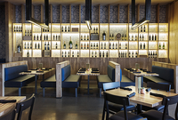 Alcohol bottles arranged on illuminated shelves in restaurant