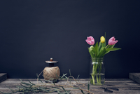 Tulips blooming in glass container by spool on wooden table against black background