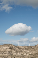 Wind turbines on mountains against cloudy sky