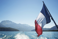 French flag over Lake Annecy against clear sky