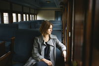 Thoughtful woman looking through window while sitting in train