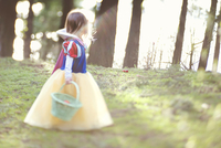 Side view of girl in dress carrying basket on field