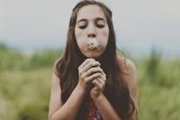 Cute girl blowing dandelion on field