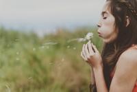 Side view of girl blowing dandelion on field