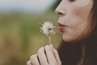 Cropped image of girl blowing dandelion on field