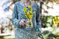 Midsection of senior woman holding flower vase and pliers at yard