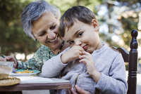 Portrait of cute boy sitting with grandmother at outdoor table