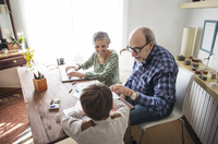 Happy grandparents assisting boy in drawing at home