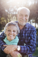Portrait of cheerful senior couple in park