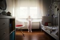 Girl hiding behind curtain at home