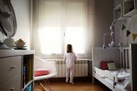 Rear view of girl looking through window in bedroom