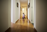 Rear view of girl sitting on bicycle in corridor at home