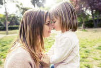 Side view of affectionate mother and daughter head to head in park