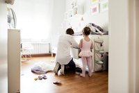 Rear view of mother searching in drawer with daughter wearing tutu in bedroom
