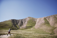 Boy walking on trail in field by mountains against clear blue sky