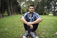 Portrait of man hugging knees while sitting on grass at park