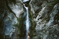 Rear view of naked woman with arms raised standing in front of waterfall