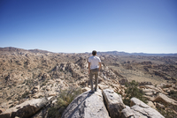 Rear view of man standing on rocks against clear blue sky