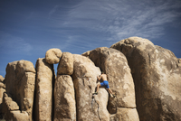 Rear view of man climbing rock outcropping against sky