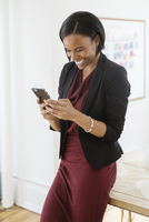 Happy businesswoman using smart phone in creative office