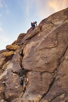 Low angle view of men climbing rock against sky