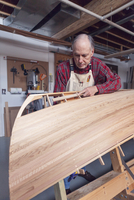 Senior man making boat in workshop
