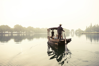 Rear view of men traveling in rowboat on river against clear sky