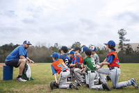 Side view of coach talking to baseball team on field