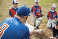 Rear view of coach pointing while discussing with baseball team on field
