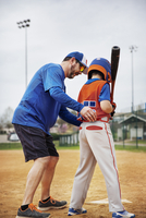 Side view of coach assisting boy in playing baseball on field