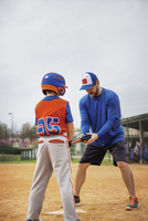Coach assisting boy in playing baseball on field